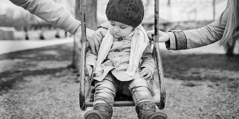 Toddler being pushed in a swing by parents