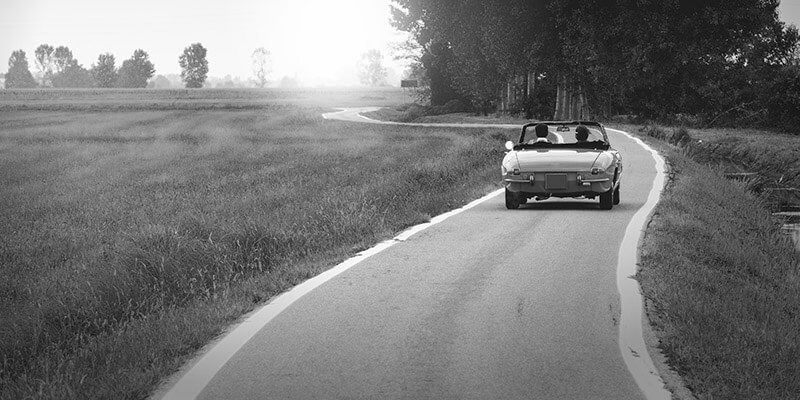 Couple driving down a country road in a classic car