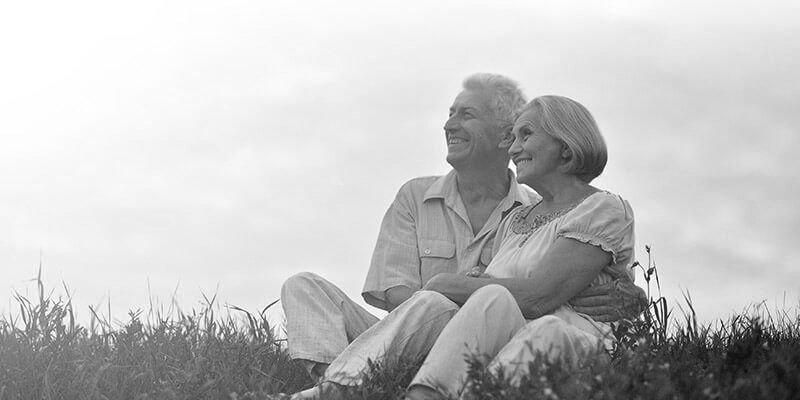 Happy retired couple sat on on the grass