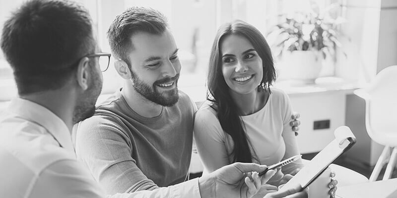 Happy couple planning their savings with a financial expert