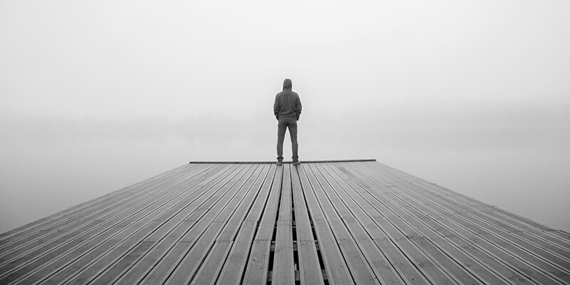 Figure stood at the end of wooden pier
