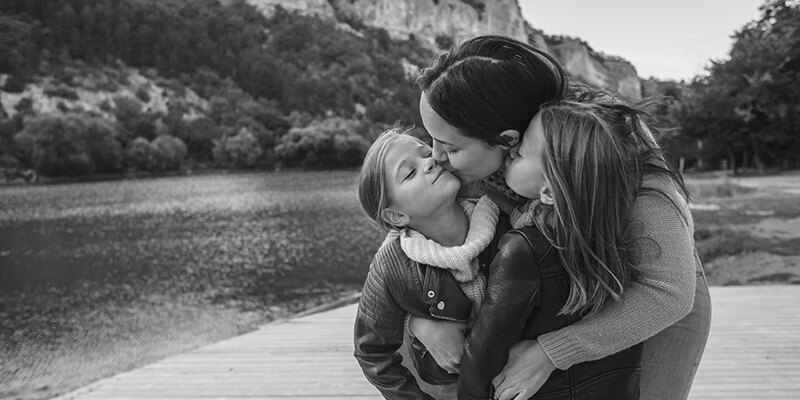 Mother embracing daughters with a kiss