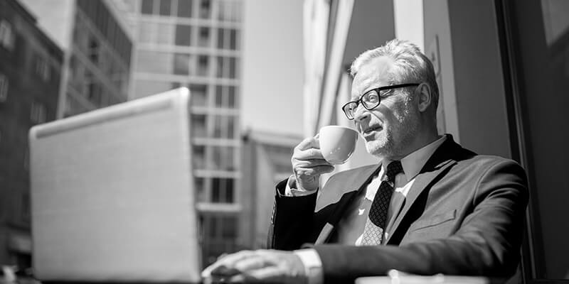 Businessman enjoying a coffee while looking at financial figures on a laptop