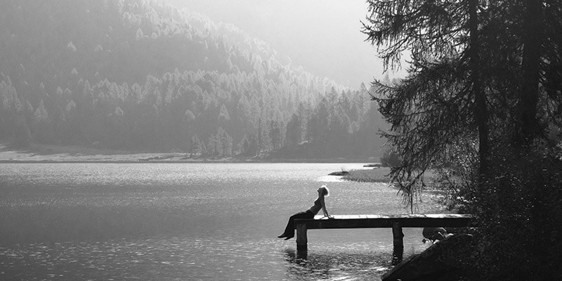 Woman sat on the end of a small pier enjoying the beautiful landscape